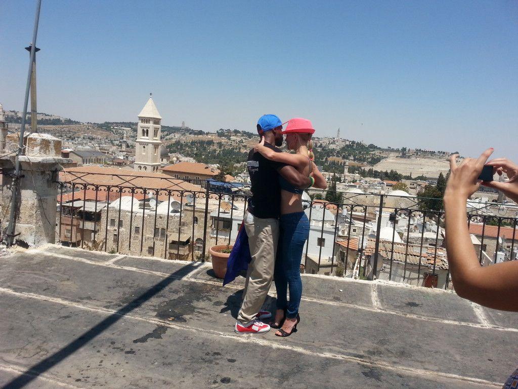 זוג מדריכי סלסה רוקדים על גג מלון פטרה אל מול העיר העתיקה