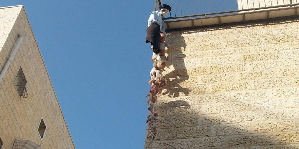 עשרת בני המן תלויים בפורים 2014 בשכונת הבוכרים. שימו לב שהמן שוטר